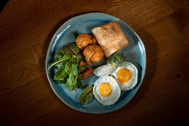 Uova strapazzate su carne con patate fritte e pane tostato