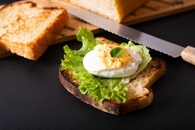 Uovo affogato casalingo o uova benedetto di concetto della prima colazione dell'alimento biologico su pane di lievito naturale tostato sul bordo nero dell'ardesia