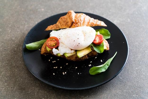 Uovo alla benedict con avocado, pomodori e insalata