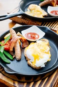 Uovo alla benedict con salsiccia e pancetta e salsa di pomodoro