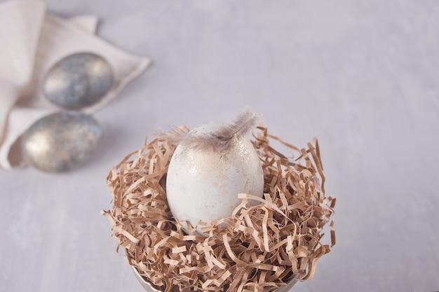 Uovo bianco di pasqua in un nido e due uova d'argento su uno sfondo grigio con piume