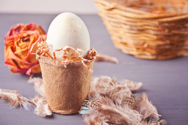 Uovo bianco di pasqua in una pentola sullo sfondo nero con cesto, rose secche e piume