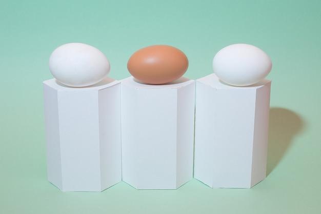 Uovo bianco e marrone su sfondo verde. forme geometriche bianche e uova. vacanze di pasqua. isolato