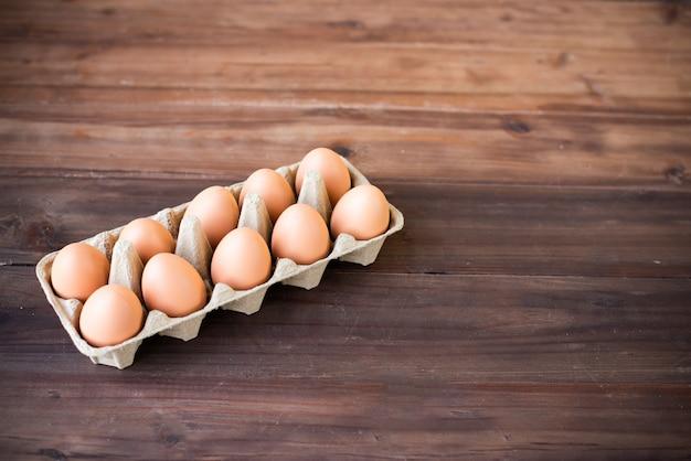 Uovo crudo nella fila nel fondo di legno