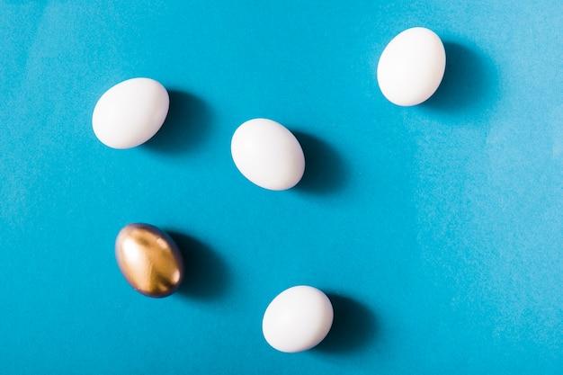 Uovo d'oro e uova bianche su sfondo blu