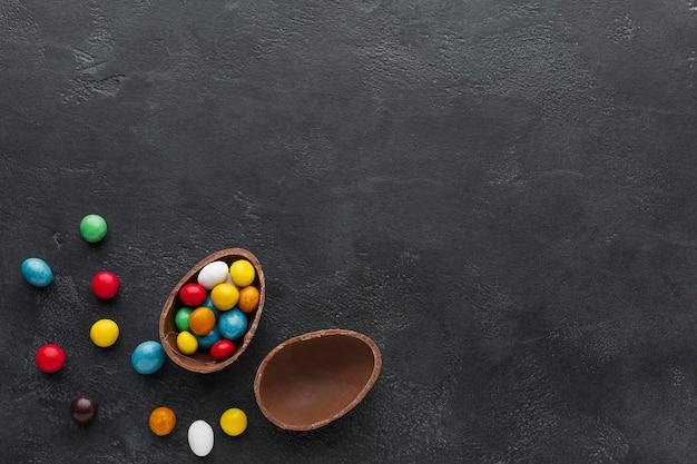 Uovo di cioccolato pasquale pieno di caramelle colorate