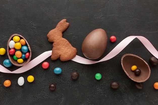 Uovo di cioccolato per pasqua e coniglietto a forma di biscotto con caramelle
