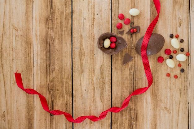 Uovo di cioccolato vicino caramelle e nastro
