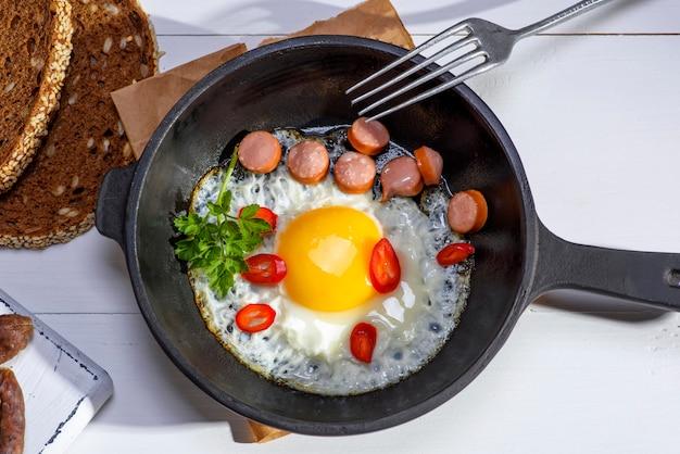 Uovo di gallina con fette di salsiccia in una padella rotonda nera in ghisa a