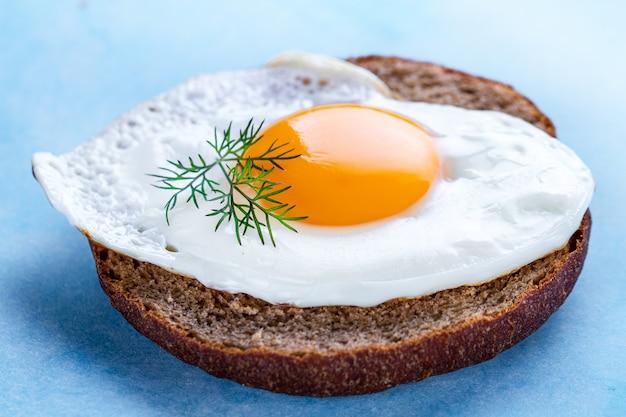 Uovo di gallina fatto in casa, fritto con panino e aneto fresco per una sana colazione. alimento proteico. panino alle uova