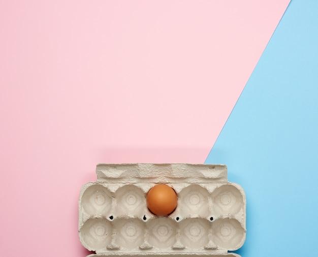 Uovo di gallina intero marrone in un vassoio di carta su uno sfondo rosa-blu