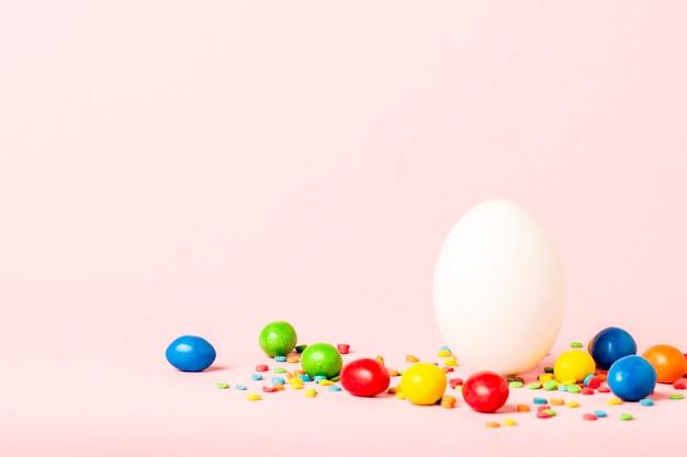 Uovo di pasqua bianco e multi dolci colorati su una superficie rosa. concetto di celebrazione di pasqua.