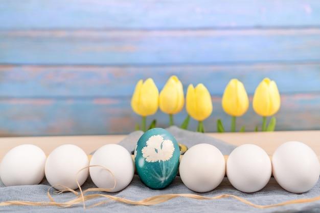 Uovo di pasqua blu biologico nel mezzo di uova di colore bianco attendere per la pittura