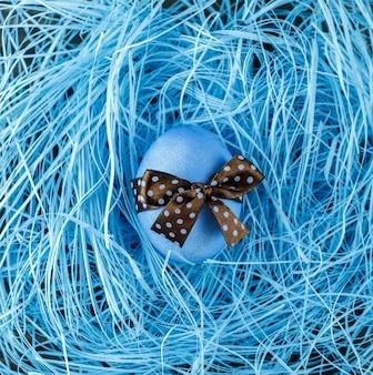 Uovo di pasqua blu con fiocco marrone su sfondo blu