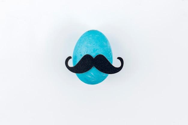 Uovo di pasqua blu con i baffi di carta sul tavolo