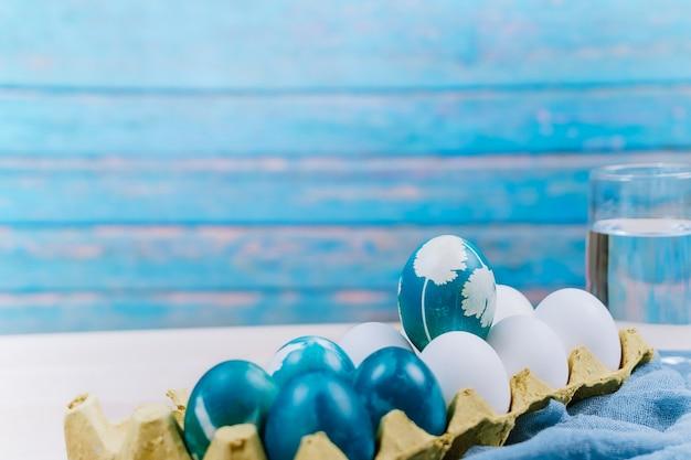 Uovo di pasqua blu organico in piedi sulle uova di colore bianco attendere per la pittura