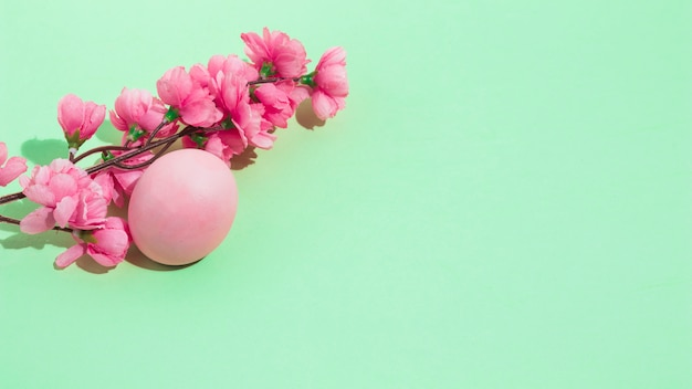 Uovo di pasqua colorato con fiori sul tavolo