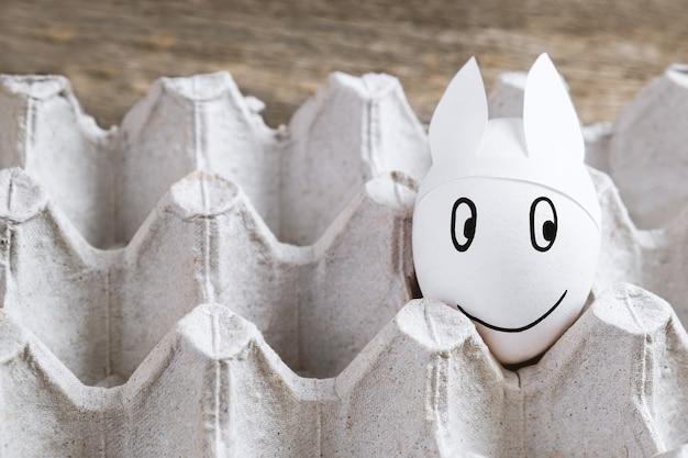 Uovo di pasqua con orecchie da coniglio nel pacchetto