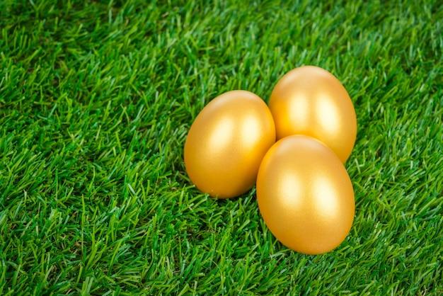 Uovo di pasqua d'oro su un prato verde