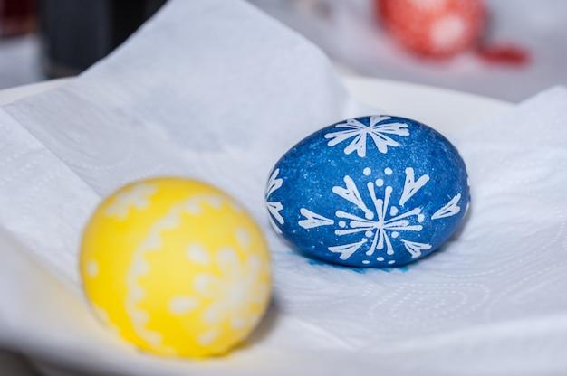 Uovo di pasqua dipinto a mano sul tovagliolo di carta bianca. il processo di dipingere le uova con la cera.