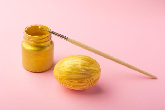 Uovo di pasqua dipinto oro e pennello. concetto di vacanza di pasqua.