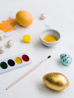 Uovo di pasqua dorato con tavolozza e pennello