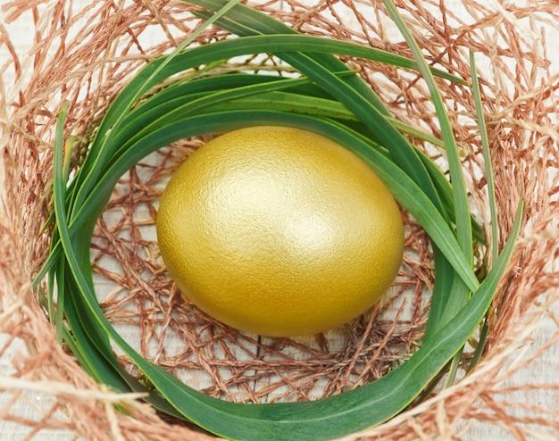 Uovo di pasqua dorato in un nido.