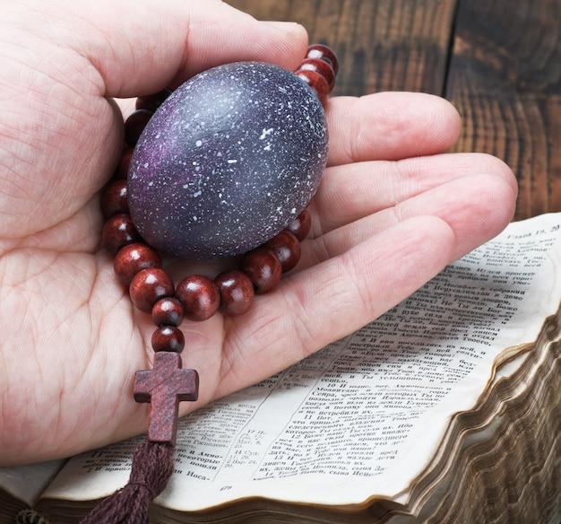 Uovo di pasqua e un rosario in una mano umana