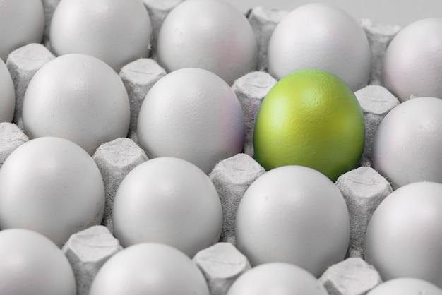 Uovo di pasqua giallo verde con riflessi dorati in una scatola con identiche uova bianche, gruppo, differenza.