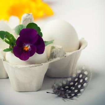 Uovo di pasqua in nido di uccelli con fiori di primavera