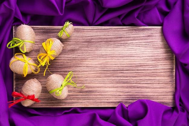 Uovo di pasqua in spago vicino a fondo di legno e porpora