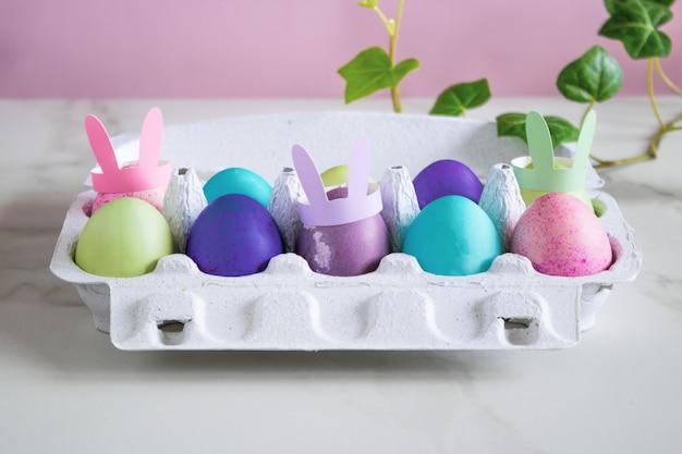 Uovo di pasqua multicolore, rosa, verde, blu, oro con orecchie da coniglio su fondo di marmo