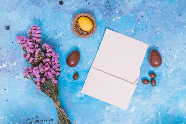 Uovo di pasqua nel nido con carta e fiori
