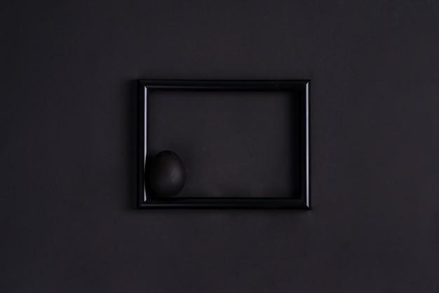 Uovo di pasqua nero di paintbrash in nero su cornice nera