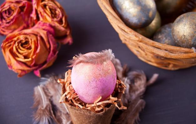 Uovo di pasqua rosa in una pentola su sfondo nero con cesto, rose secche e piume