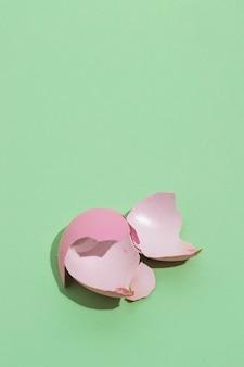 Uovo di pasqua rosa rotto sul tavolo
