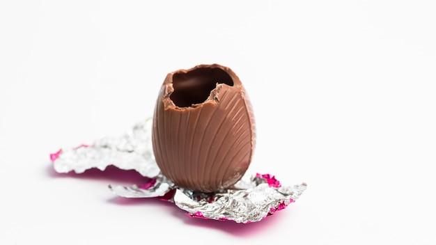 Uovo di pasqua scartato in carta rosa con morso estratto