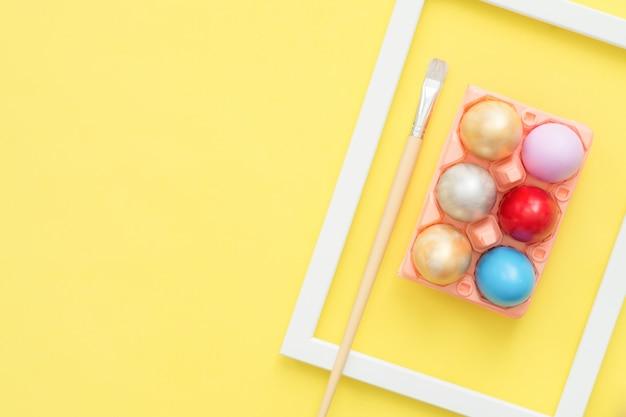 Uovo di pasqua variopinto di vista superiore piana di disposizione dipinto in composizione in colori pastello con il pennello su giallo
