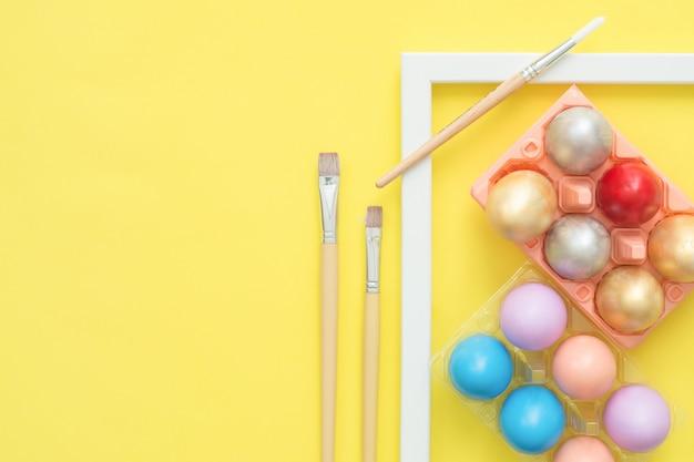 Uovo di pasqua variopinto di vista superiore piana di disposizione dipinto in composizione in colori pastello con il pennello