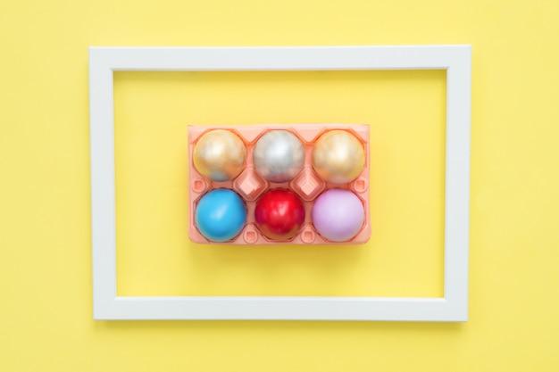 Uovo di pasqua variopinto di vista superiore piana di disposizione dipinto in composizione in colori pastello su colore pastello giallo