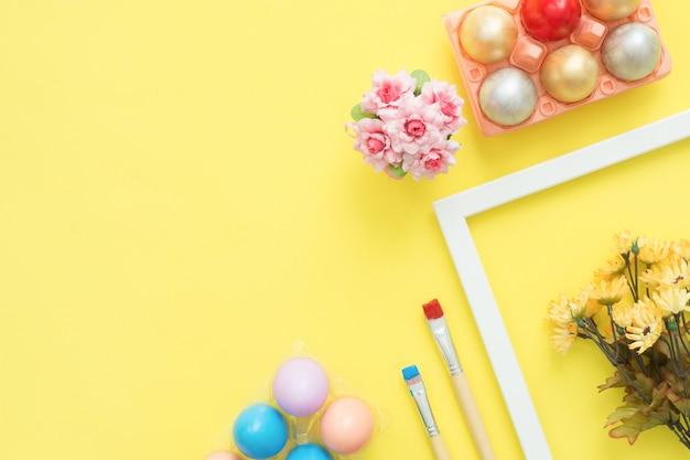 Uovo di pasqua variopinto di vista superiore piana di disposizione dipinto nei fiori della composizione e della molla di colori pastelli