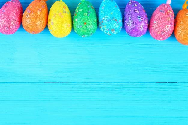 Uovo di pasqua variopinto sul fondo di legno di colore pastello blu con spazio
