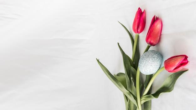 Uovo di pasqua vicino mazzo di fiori