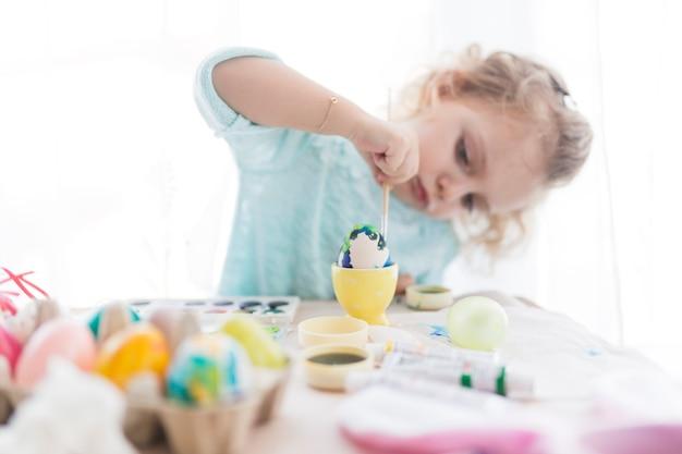 Uovo di pittura ragazza concentrato