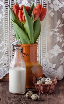 Uovo di quaglia con una bottiglia di latte e fiori