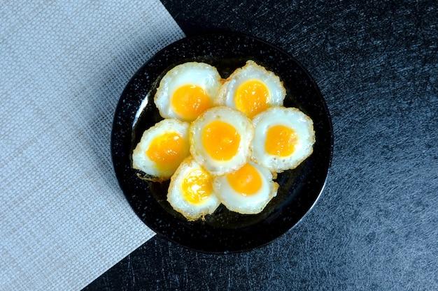 Uovo di quaglia fritto su sfondo nero