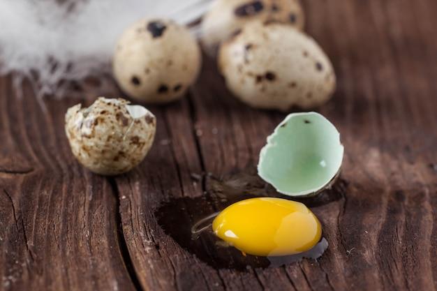 Uovo di quaglia rotto con il tuorlo fuoriuscito