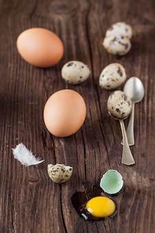 Uovo di quaglia rotto con il tuorlo trapelato e le uova di gallina