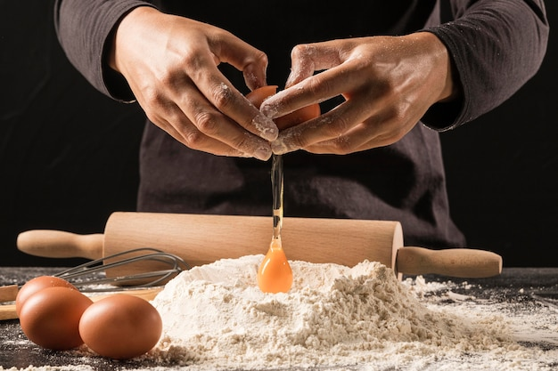 Uovo di versamento del cuoco unico del primo piano su farina