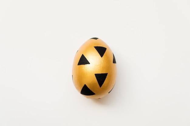 Uovo dorato di pasqua con il reticolo nero triangolare isolato su priorità bassa bianca